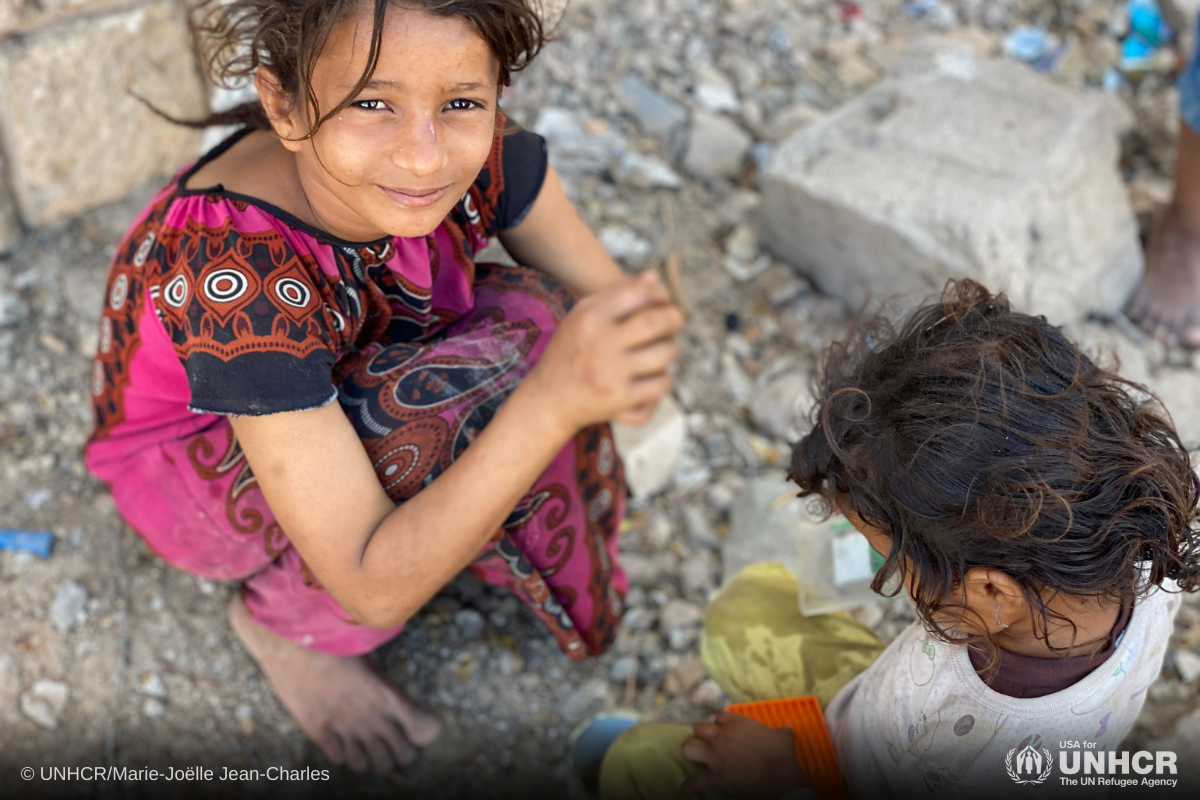 9-year-old internally displaced girl, Ipteehal, plays kitchen with her younger sister Radia outside the unfinished building where they live with other displaced families in Al Mukalla, Hadramaut, Yemen